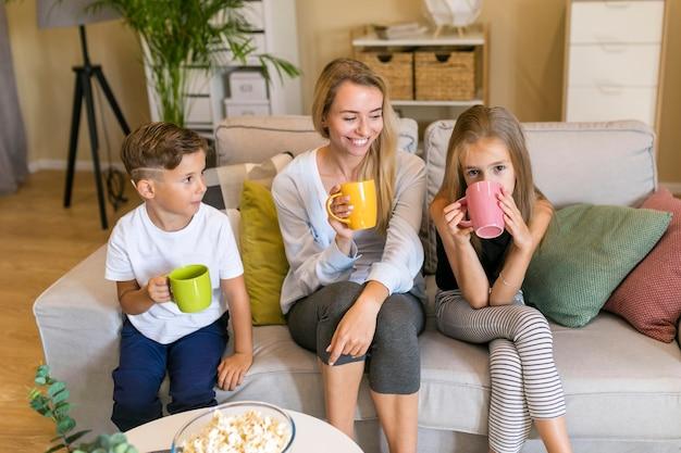 Mãe e filhos sentados em um sofá vista frontal