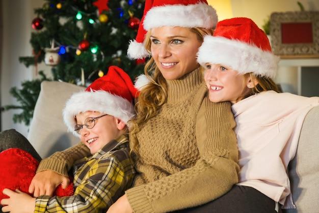 Mãe e filhos sorrindo com chapéus de santa