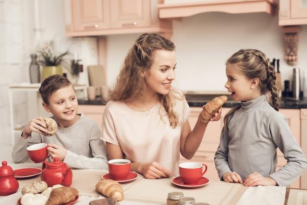 Mãe e filhos têm chá e croissants em casa.