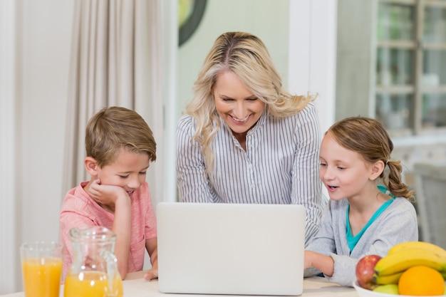 Mãe e filhos usando laptop enquanto tomando café da manhã