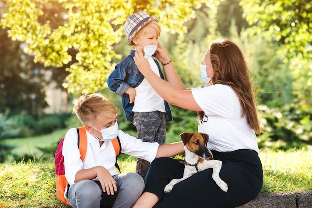 Mãe e filhos usando máscara médica protetora de rosto.