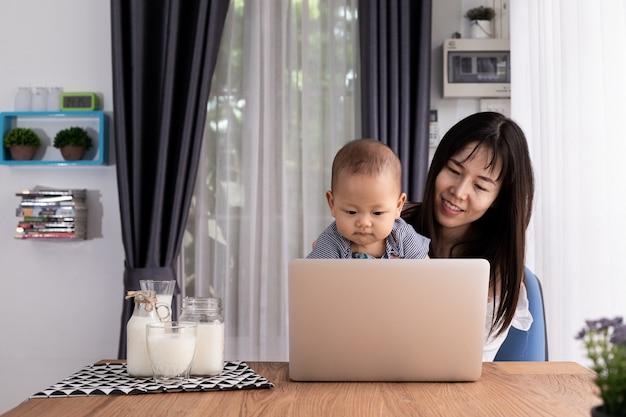 Mãe e filhos usando o laptop em casa.