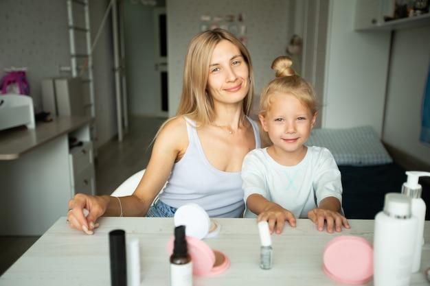 Mãe e linda filhinha na mesa em casa