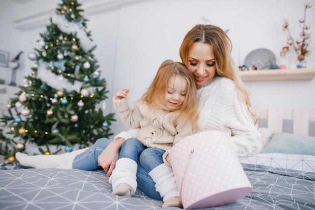 Mãe e linda garota loira que abre presentes