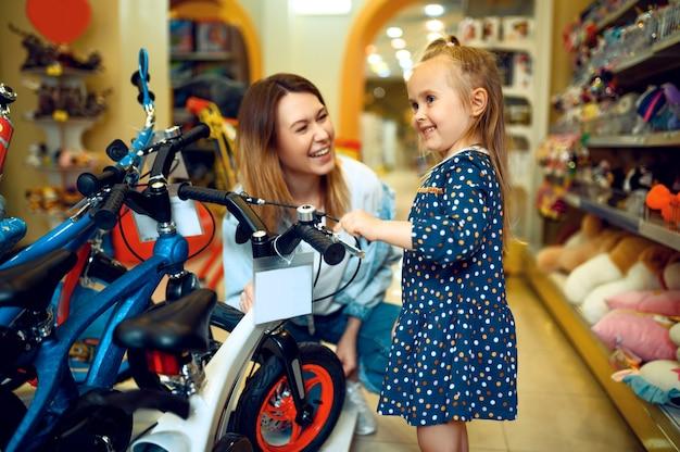 Mãe e linda garotinha escolhendo bicicleta em loja infantil