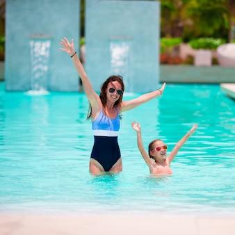 Mãe e menina, aproveitando as férias de verão na piscina de luxo