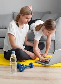 Mãe e menina assistindo vídeos de esporte