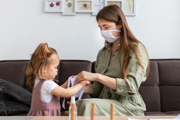 Mãe e menina com máscaras médicas