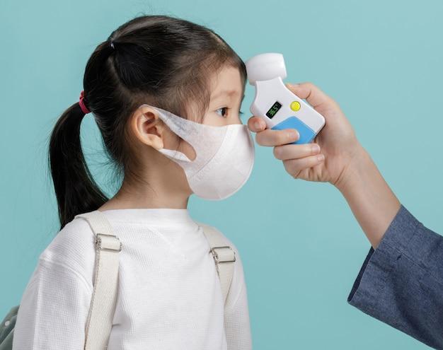 Mãe e menina criança asiática vestindo máscara respiratória para proteger surtos de coronavírus e temperatura corporal verificada em meio ao novo vírus covid-19