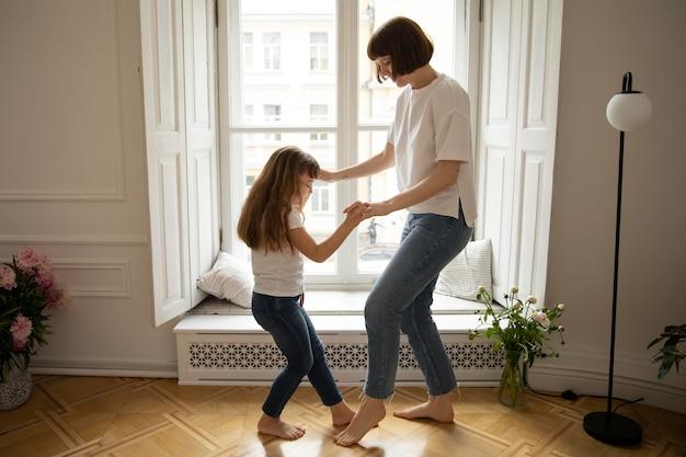 Mãe e menina dançando dentro de casa