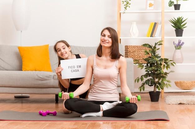 Mãe e menina em casa treinando