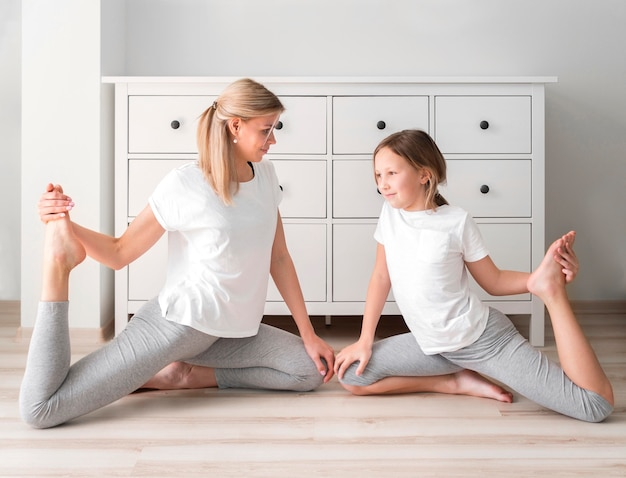Mãe e menina esporte treinando em casa