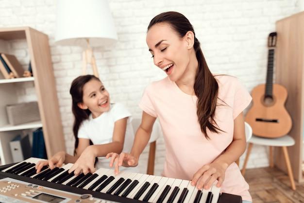 Mãe e menina estão jogando o sintetizador em casa