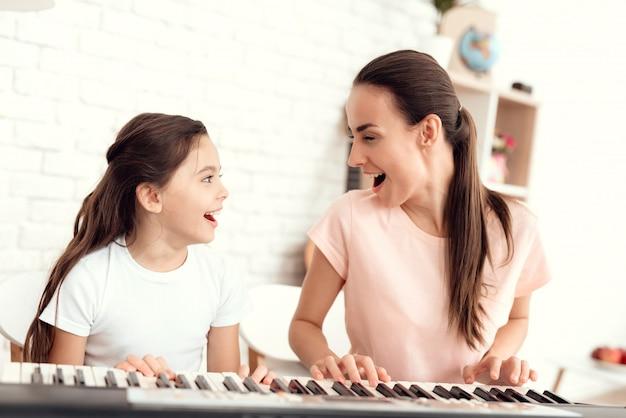 Mãe e menina estão jogando o sintetizador juntos.