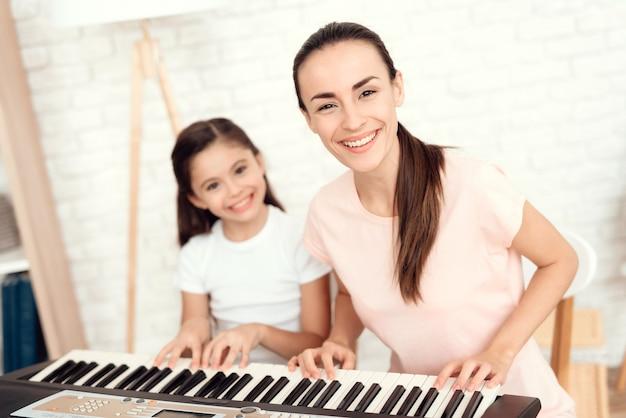 Mãe e menina estão tocando piano e descansar e se divertir.