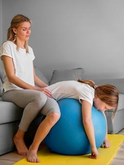 Mãe e menina exercitam na bola