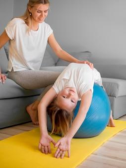 Mãe e menina exercitam-se na bola em casa