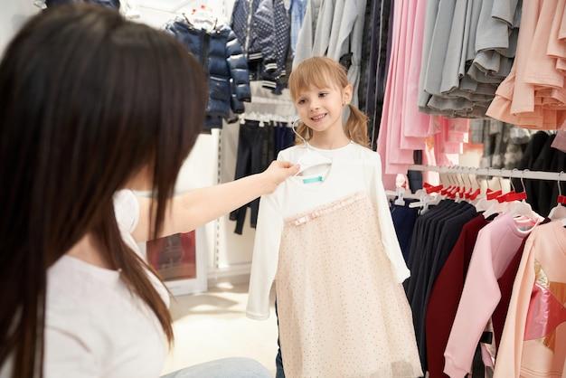 Mãe e menina olhando, escolhendo o vestido rosa.
