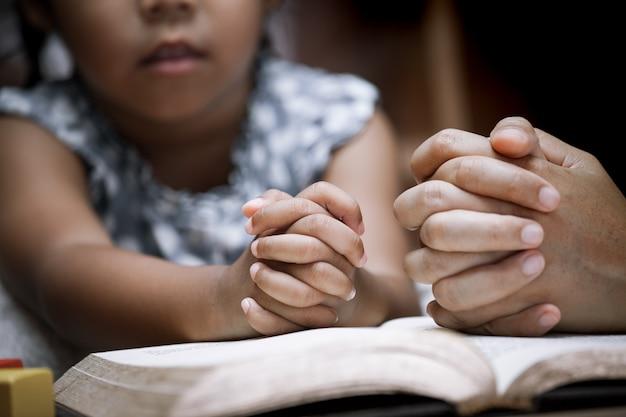 Mãe e menina oram junto com uma bíblia sagrada