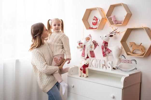 Mãe e menina pequena em casa na época do natal