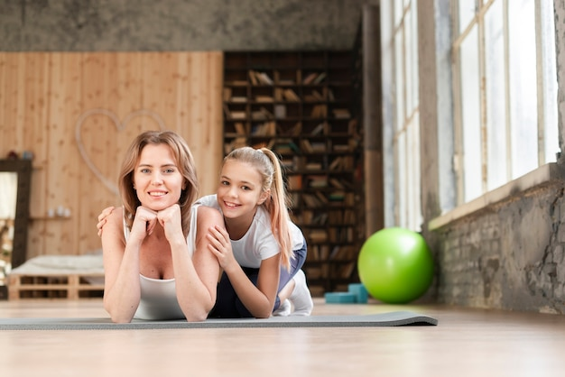 Mãe e menina posando em tapetes de ioga