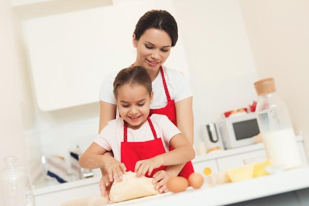 Mãe e menina preparam a massa em aventais vermelhos.
