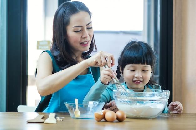 Mãe e menina se ajudam a fazer bolos na cozinha em casa.