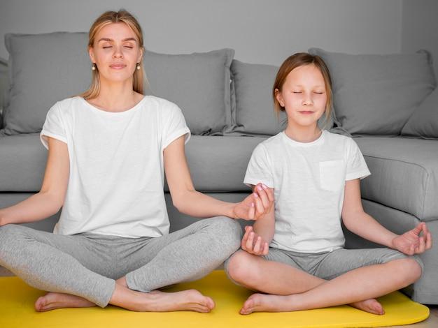 Mãe e menina, treinamento de yoga