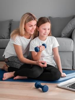 Mãe e menina treinando após vídeos do laptop