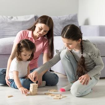Mãe e meninas brincando no chão