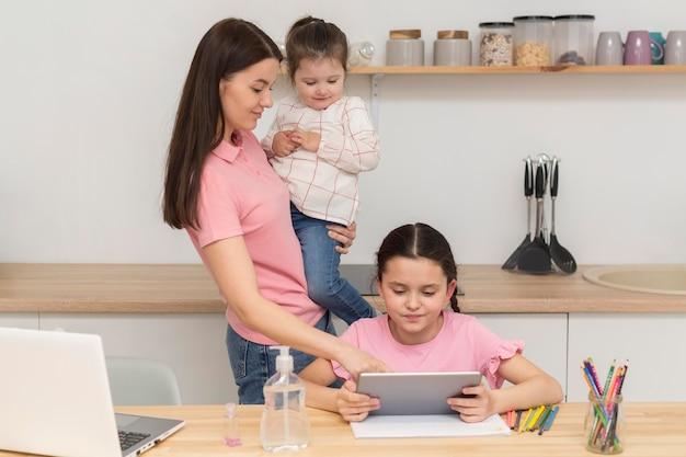 Mãe e meninas com dispositivos