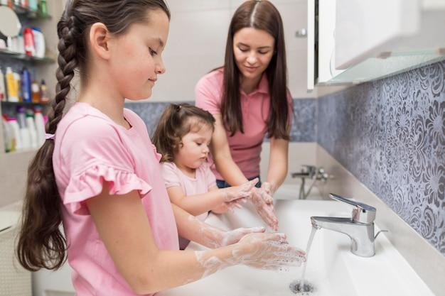 Mãe e meninas lavando as mãos