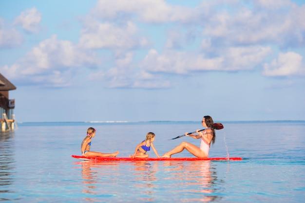 Mãe e meninas na prancha de surf durante as férias de verão