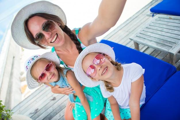 Mãe e meninas tomando selfie na praia tropical
