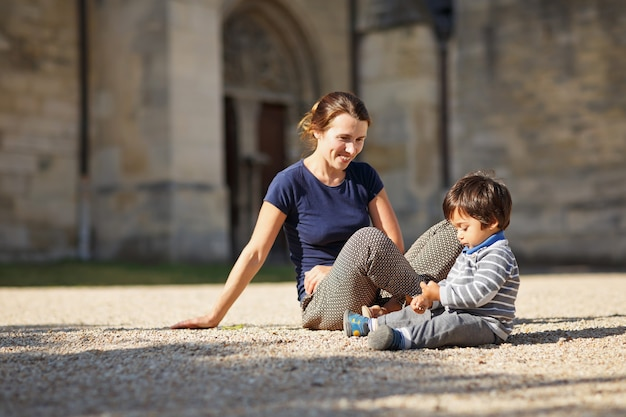 Mãe e menino lindo oriental brincando ao ar livre no parque