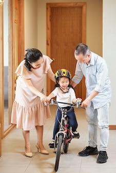 Mãe e pai ajudando a filha no capacete a andar de bicicleta no corredor do apartamento