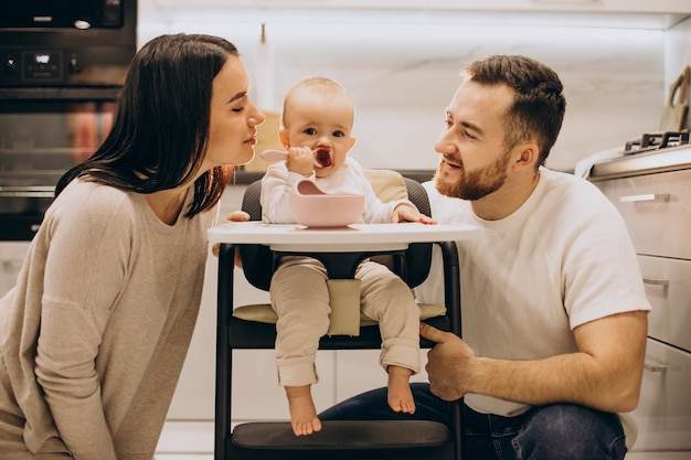 Mãe e pai alimentando sua filha em uma cadeira de alimentação