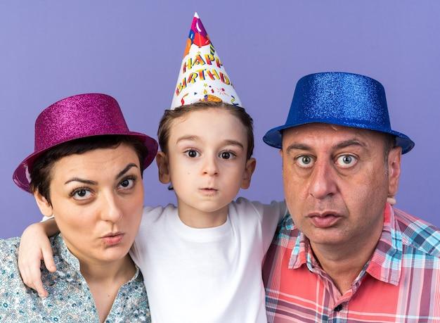 Mãe e pai ansiosos com chapéus de festa em pé com o filho isolado na parede roxa com espaço de cópia