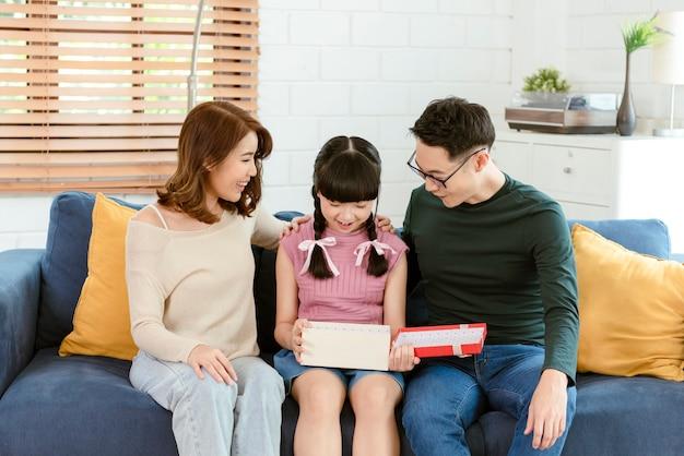Mãe e pai asiáticos dão um presente para a filha. conceito caixa de presente surpresa para feliz aniversário.