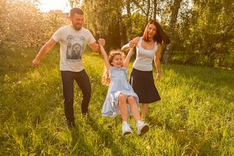 Mãe e pai balançando sua filha entre eles