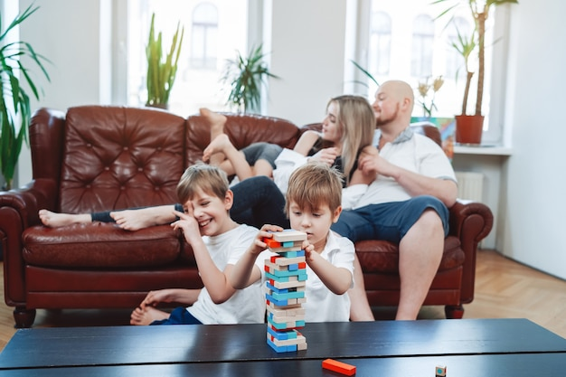 Mãe e pai brincam com o filho, enquanto outros dois meninos jogam jenga sentados à mesa.