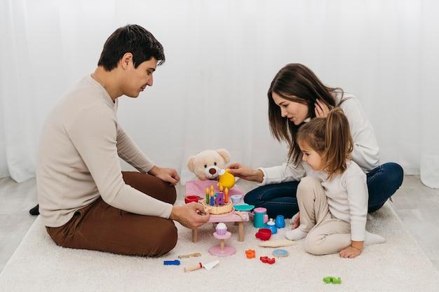 Mãe e pai brincando com a filha em casa
