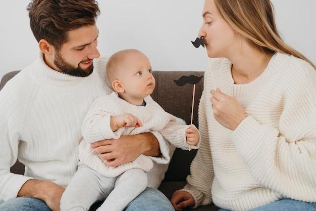 Mãe e pai brincando em casa com o bebê