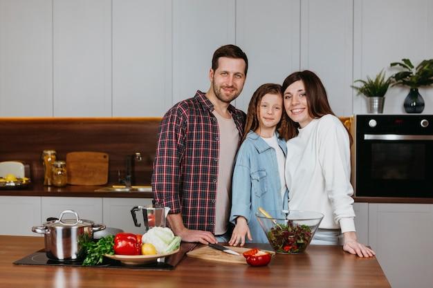 Mãe e pai com filha posando na cozinha