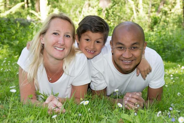 Mãe e pai com filho misto menino na grama no verão com amor