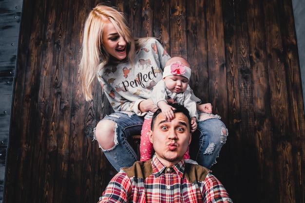 Mãe e pai com seu bebê em uma cadeira de bar no contexto de uma parede de madeira
