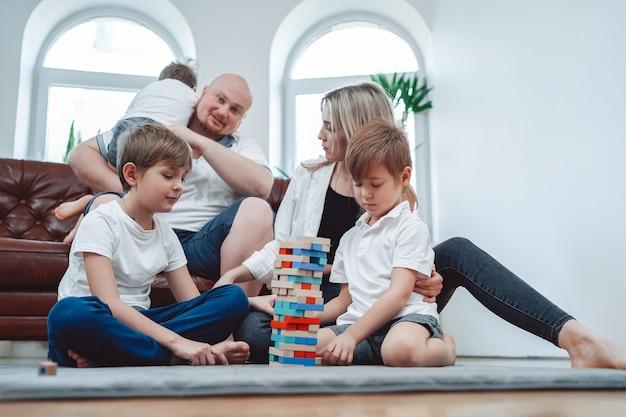 Mãe e pai com seus três filhos. família feliz e amorosa joga jenga em casa juntos e se divertindo.