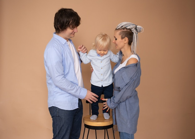 Mãe e pai e filho pequeno isolado em bege