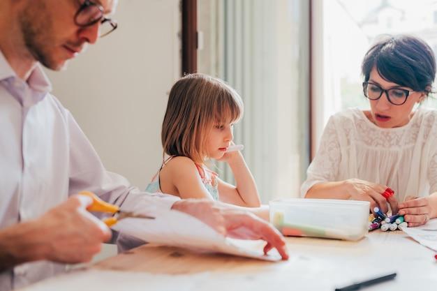 Mãe e pai em casa, educando seus filhos do sexo feminino indoor - ensino, tutoria, conceito de educação