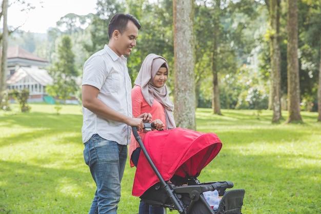 Mãe e pai empurrando carrinho de bebê no parque